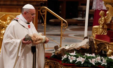 Papa Francis coloca uma estátua do bebê Jesus diante do altar da Basílica de São Pedro no início da Missa (CNS / Paul Haring)