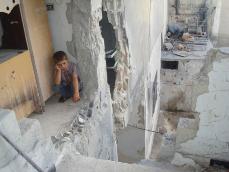 BOY SITS IN DAMAGED HOME AFTER SHELLING IN SYRIA