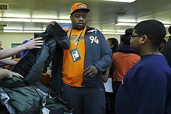 A Denver Bronco helps a boy find a coat during a service event  Jan. 28 with Knights of Columbus in jersey City, N.J. (CNS photo/Reuters)