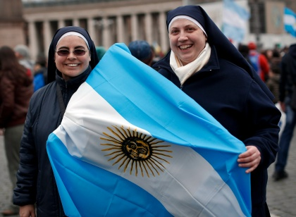 Nuns carrying an Argentine flag smile after Pope Francis leads Angelus at Vatican