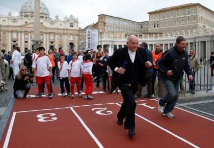 Priest runs in 100-meter relay race on main road leading to St. Peter's Square at Vatican