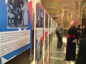 Archbishop Mamberti looks at the photo exhibit. (CNS/CindyWooden)