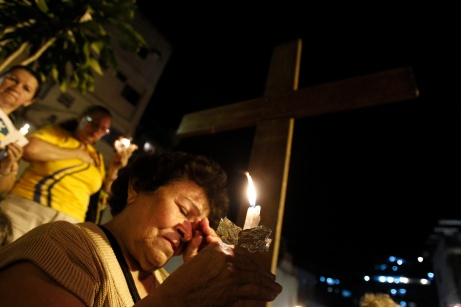 Woman prays in front of World Youth Day cross during visit to Rocinha slum in Rio de Janeiro