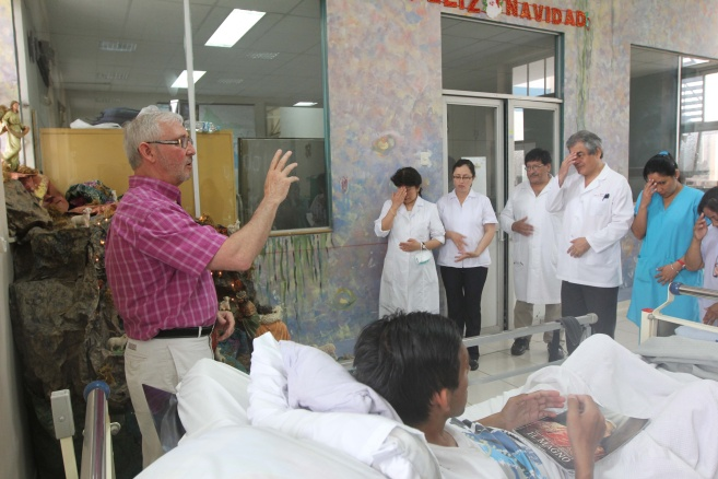 Priest prays with staff and patients in infectious diseases ward of Lima hospital