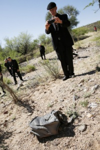 Bishop John C. Wester of Salt Lake City takes a picture of a discarded backpack in the Arizona desert. (CNS photo/Nancy Wiechec)