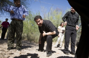 Bishop Oscar Cantu of Las Cruces, N.M., ducks under barbed wire as a group of U.S. bishops tours an area of the Arizona desert north of Nogales. (CNS photo/Nancy Wiechec)