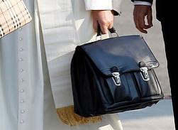 Pope Francis holds personal bag as he boards plane at airport in Rome