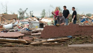 A man tosses aside bricks while searching in the rubble of a destroyed house April 28 after a tornado hit the town of Vilonia, Ark., the previous day. A series of tornadoes ripped through Arkansas, Oklahoma and Kansas. killing at least 18 people and injuring more than 100. (CNS/ Reuters)