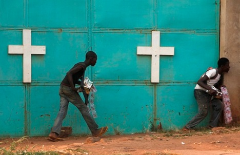 People hide from gunfire near a church during a Feb. 18 firefight between African peacekeepers and fighters from the Anti-Balaka militia in Bangui, Central African Republic.  (CNS/Reuters)