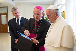 President of Pontifical Council for Social Communications shows Pope Francis news on tablet during meeting at the Vatican