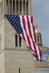 Large U.S. flag blows in wind outside national shrine in Washington on eve of 9/11 anniversary. (CNS photo/Bob Roller)