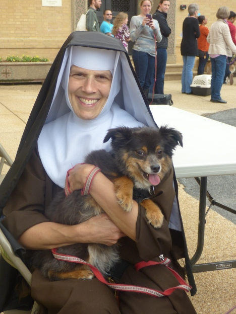 Sister St. John, of the Poor Clares of Perpetual Adoration, holds Marlie during the blessing of the animals at the Franciscan Monastery.