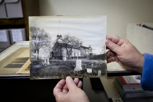 Jesuit priest holds historic photo of St. Ignatius Church. (CNS photo/Tyler Orsburn)