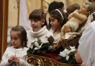 Children gather near a figurine of the baby Jesus at the conclusion of Pope Francis' celebration of Christmas Eve Mass in St. Peter's Basilica at the Vatican Dec. 24. (CNS photo/Paul Haring)