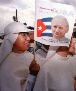A nun waves a flag bearing the image of Pope John Paul II during his 1998 trip to Cuba. (CNS/Reuters)