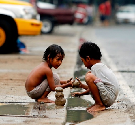 Filipino children play with mud in slum area of Manila, Philippines, May 29. (CNS/EPA)