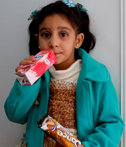 A Syrian refugee girl sips a drink at a school in northern Jordan. (CNS/Barb Fraze)