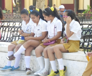 A group of schoolgirls cup their cellphones in their hands to protect from the sun's glare in Cuba. While few Cubans have access to the latest  gadgets, Catholics have long used technology in various forms to transmit the faith.  (CNS photo/ Rhina Guidos)