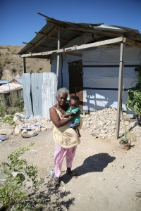 Charity Dorelien stands with her grandchild outside her makeshift home in Canaan, a community on the outskirts of Port-au-Prince, Haiti, Feb. 17.  (CNS/Bob Roller)