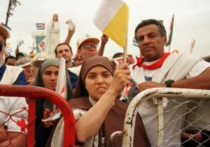Una monja mueve la bandera del Vaticano mientras asiste a la misa de Papa Juan Pablo II en La Habana el 25 de enero de 1998. El Vaticano confirmó que Papa Francisco visitará Cuba en septiembre. (CNS/Alyssa Banta)
