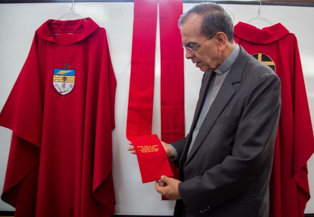 Bishop Gregorio Rosa Chávez, Auxiliary Bishop of San Salvador, looks at the vestments bishops and priests will wear for the beatification of El Salvador's Archbishop Óscar Romero on May 23.  (Photo courtesy of Beatificación Romero)