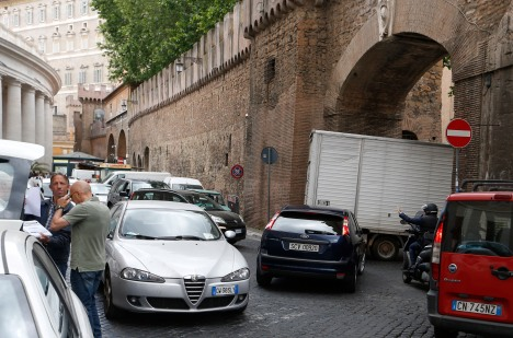 "Pope Francis' blue Ford Focus with its ""SCV"" plate gets stuck in the traffic, but the moped guy waves. (CNS/Paul Haring)"