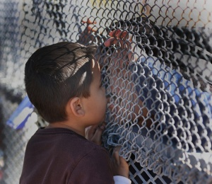 A boy in New Mexico kisses his father through the border fence following Mass Nov. 22 in Sunland Park, New Mexico. The photo was part of a package honored by the CPA.  (CNS photo/Bob Roller)