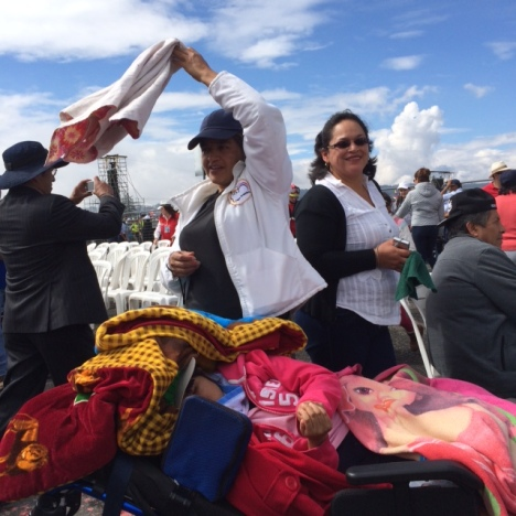 A woman attending the Mass in Quito with her disabled daughter waves a cloth in time to the music.  (CNS photo/Barbara J. Fraser)