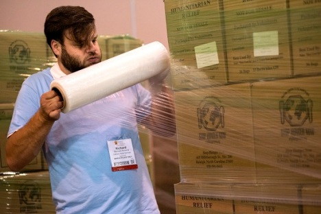 Richard Armenia plastic-wrapped the filled boxes to send off to Burkina Faso as volunteers reached the one-hour mark of Thursday's Helping Hands event. (CNS photo/Carley Mossbrook)