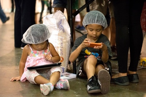 Two very young volunteers take a break during the packing of the meals. (CNS photo/Carley Mossbrook)