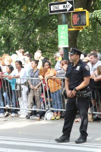 Crowds wait for Pope Francis' motorcade to appear while a New York City police officer patrols the area on Sept. 25. Ticket-holders stood for hours just to get a glimpse of the pontiff as he made his way towards Madison Square Garden. (CNS photo/Seth Gonzales)