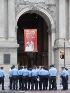 Philadelphia police officers get instructions outside of City Hall as a banner welcomes Pope Francis to the city of brotherly love. (CNS/Dennis Sadowski)