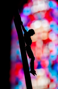Crucifix is silhouetted against stained-glass window in chapel ay New York correctional facility. (CNS photo/Mike Crupi)