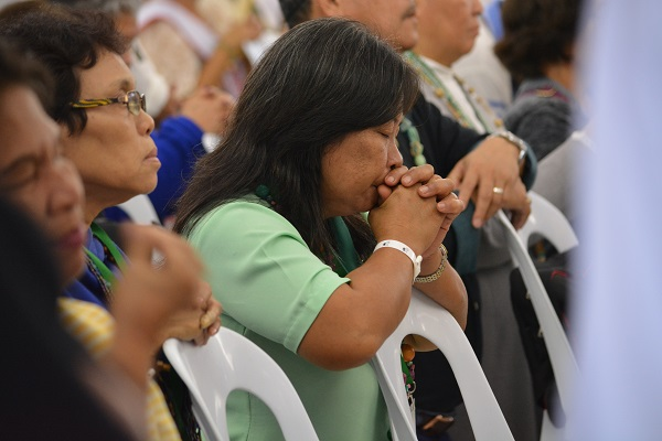 A woman prays while waiting to take Communion during a Jan. 27 fellowship night between 51st International Eucharistic Congress delegates and parishioners of Our Lady of the Sacred Heart in Cebu, Philippines. (CNS photo/Simone Orendain)