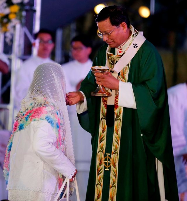Cardinal Charles Bo of Yangon, Myanmar, gives Communion during the 51st International Eucharistic Congress opening Mass in Cebu, Philippines, Jan. 24. (CNS photo/Francis R. Malasig, EPA)