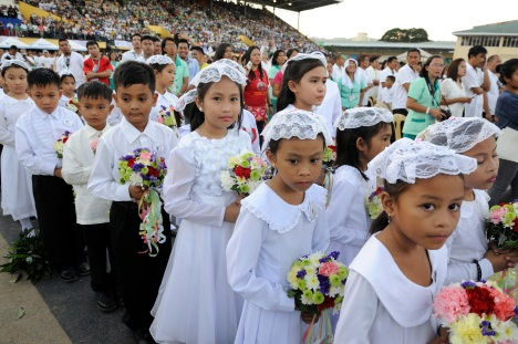 First communicants carry flowers during a children's first Communion Mass at the International Eucharistic Congress in Cebu, Philippines, Jan. 30. (CNS photo/Katarzyna Artymiak)