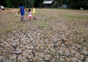 A woman and children walk through a drought-stricken rice field April 3 in Cebu, Philippines. (CNS/Jay Rommel Labra, Reuters)