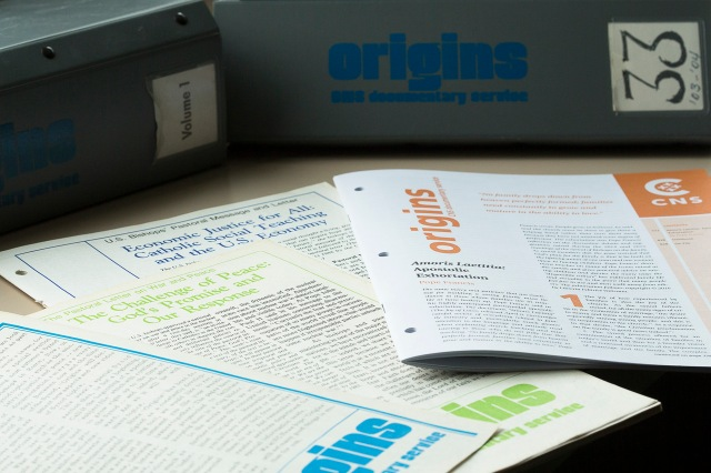Covers of some editions of Origins, along with binders for entire volumes (CNS photo/Tyler Orsburn)