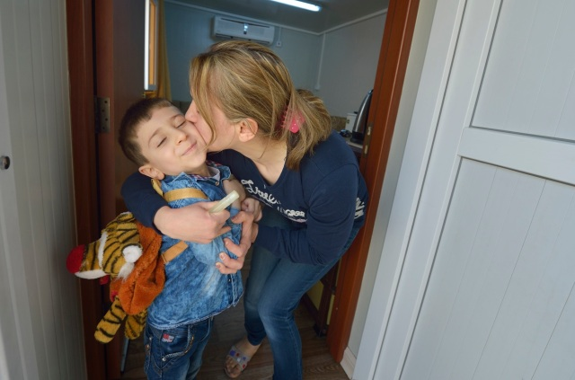 Raeda Firas kisses her 4-year old son, Luis, as he leaves their modular home April 7 to attend a church-run preschool in Ankawa, Iraq. The family was displaced by the Islamic State group in 2014 and lives in a church-provided modular home. (CNS photo/Paul Jeffrey)