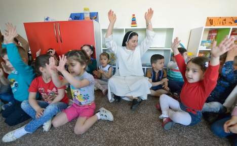 Sister Ferdos Zora sings along with students April 7 in a preschool for displaced children run by the Dominican Sisters of St. Catherine of Siena in Ankawa, Iraq. (CNS photo/Paul Jeffrey)