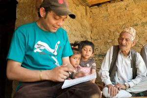 Nepalese resident Bal Bahadur Budathoki Chetri, 97, flanked by his grandchildren answers Caritas questions April 8. His house was destroyed during the 2015 earthquake. (Photo courtesy of Matthieu Alexandre, Caritas Internationalis)