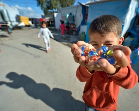 A boy plays with marbles in a camp for internally displaced families in Ankawa, Iraq, April 8. (CNS photo/Paul Jeffrey)