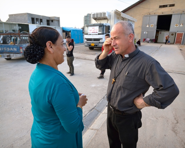 Rogationist Father Jalal Yako talks to an internally displaced woman in Ankawa, Iraq, April 8. (CNS photo/Paul Jeffrey)