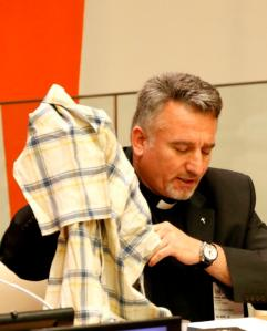 Chaldean Father Douglas Bazi holds a shirt he wore while enduring torture as a hostage in Iraq in 2006 during a conference at the United Nations April 28. (CNS/Gregory A. Shemitz)