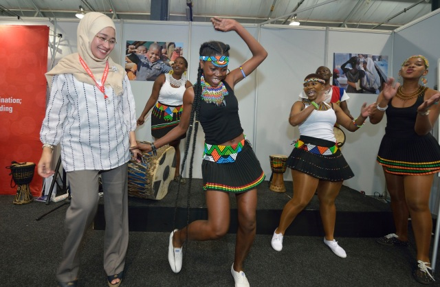 Anggia Ermarini, a Muslim activist from Indonesia, gets a lesson in African dancing at the Interfaith Networking Zone during the 2016 International AIDS Conference in Durban, South Africa, July 20. (CNS photo/Paul Jeffrey)