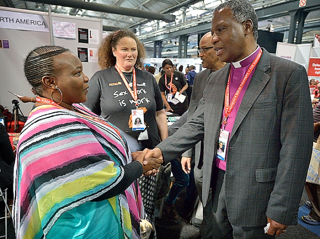 Archbishop Thabo Makgoba, Anglican archbishop of Cape Town, greets Babalwa Matikinca, an area manager for the Sex Workers Education and Advocacy Task Force. The encounter took place in the Global Village of the 2016 International AIDS Conference in Durban, South Africa. (CNS photo/Paul Jeffrey)