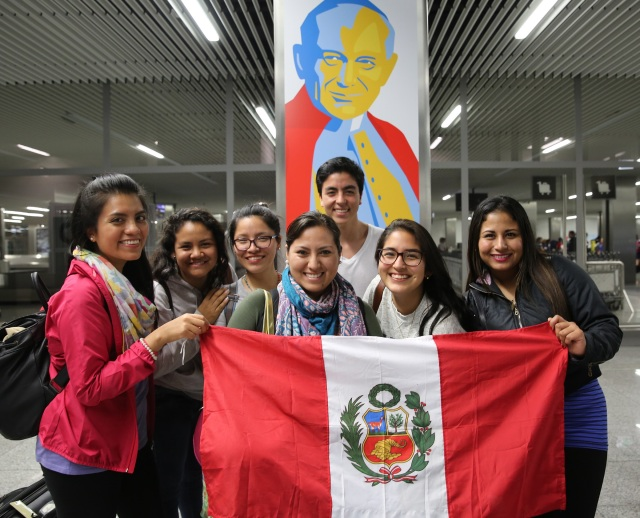 World Youth Day pilgrims from Lima, Peru, pose for a photo in front of an image of St. John Paul II after arriving July 23 at John Paul II International Airport in Krakow, Poland. (CNS photo/Bob Roller)