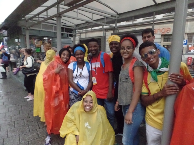 Pilgrims sporting ponchos the color of World Youth Day did not have their spirits dampened by rain July 26. (CNS photo/Dennis Sadowski)