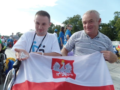 Andrej Witas, 26, with his father, Tadeusz, holds the rosary he received from Pope Francis July 28 when they both rode a tram through Krakow, Poland, to the welcoming ceremony for World Youth Day. (CNS photo/Dennis Sadowski)