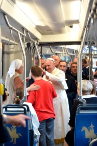Pope Francis greets a young man while riding a tram to reach the World Youth Day welcoming ceremony with young people in Blonia Park in Krakow, Poland, July 28. (CNS photo/Alessia Giuliani, pool)